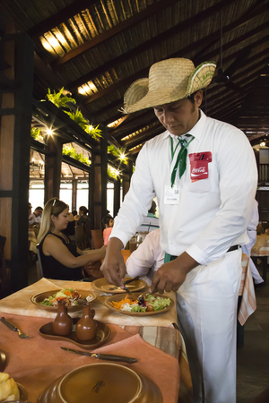 BOLIVIA, SANTA CRUZ DE LA SIERRA, 18 JANUARY 2017 - Traditional cuisine of Latin America. Waiter preparing food in one of the best restaurants in Santa Cruz, Bolivia Editorial