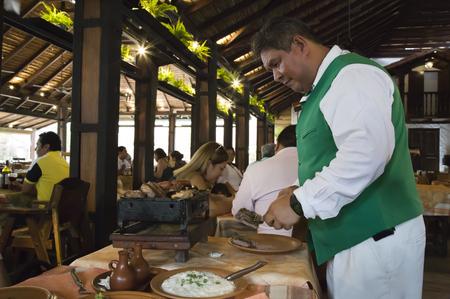 BOLIVIA, SANTA CRUZ DE LA SIERRA, 18 JANUARY 2017 - Traditional food of Latin America. Waiter preparing barbecue in a famous restaurant in Santa Cruz, Bolivia Editorial