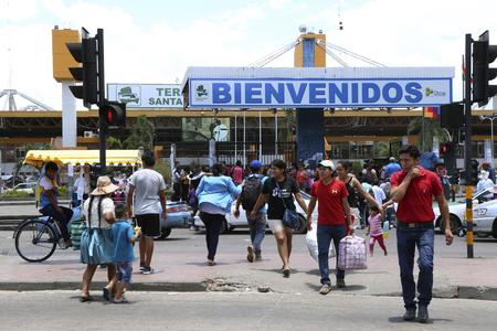 BOLIVIA, SANTA CRUZ DE LA SIERRA, 21 JANUARY 2017 - People cross road near Terminal Bimodal Santa Cruz de la Sierra - central bus and train station of Santa Cruz de la Sierra in Bolivia Redakční