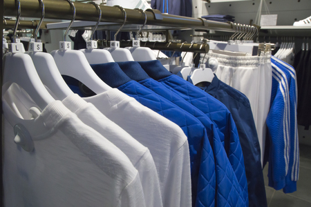 Male clothes and sportswear on hangers in a shopping mall Reklamní fotografie
