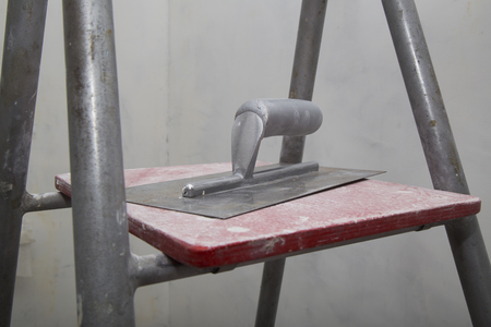 Float for applying putty at the concrete walls at the ladder during the renovation of an apartment