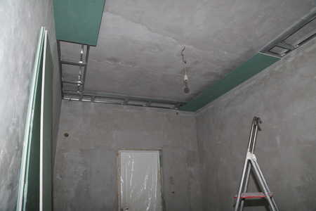 Fixing plaster boards at the ceiling of a house under construction. Reklamní fotografie