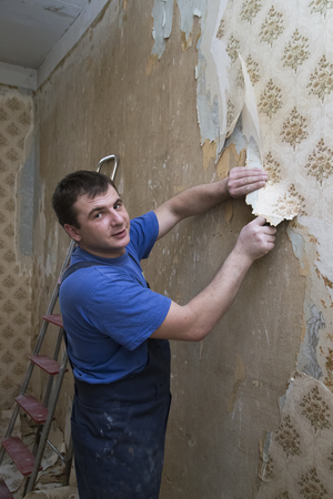 Man working on a wall of a house