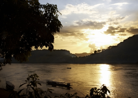 One evening in Laos while boats are crossing the river Stock Photo - 16389577