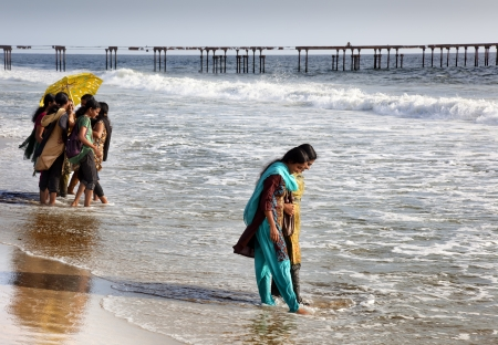 appears: Allepey, India-September 6, 2012. Many Indian tourists come to the beach for a walk or swim. One of them appears as a wave wets her feet Editorial
