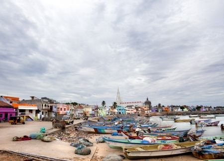 Kanyakumari, India-September 9, 2012. Dozens of fishing boats moored in the sand and the sea while the townspeople performs his duties as a normal day