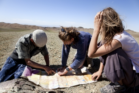 Gobi Desert, Mongolia, August 6, 2010. two girls and a man looking at a map of the Gobi desert to continue their journey