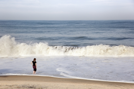 a girl on the beach as a wave breaks Stock Photo