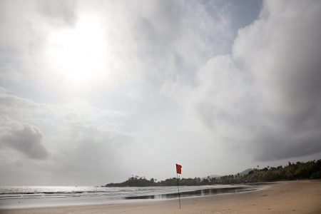 Patnem beach in Goa during the monsoon. The red flag warns of danger to swimmers photo