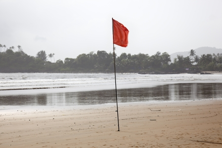 warns: Patnem beach in Goa during the monsoon. The red flag warns of danger to swimmers Stock Photo