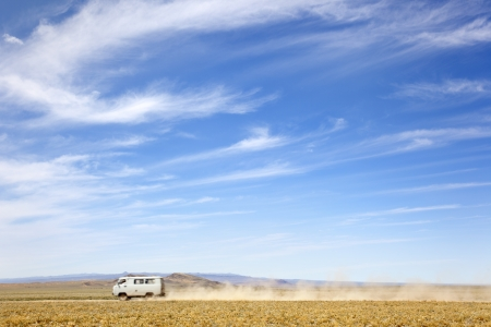 independent mongolia: a van across the desert at high speed leaving a trail of dust Stock Photo