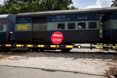 Allepy, India-September 6, 2012. A train crosses the road making vehicles and pedestrians wait behind the stop sign Stock Photo - 16425518