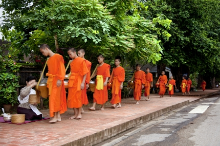 Luang Phabang, Laos-July 23, 2009  Every day very early in the morning, hundreds of monks walk the streets to beg