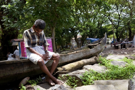 Cochin, India - September 05, 2012  An old fisherman falls asleep sitting atop his canoe Stock Photo - 16425519