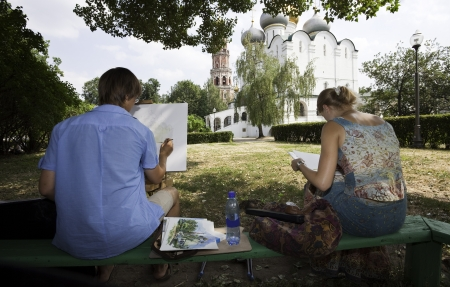 Moscow, Russia - July 21, 2010  Two young art students, sitting on a bench, drawing the Smolensk cathedral on canvas