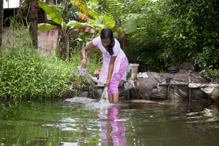 Allepey, India-September 7, 2012. An Indian woman washes her clothes on a rock in one of the canals around Alappuzha
