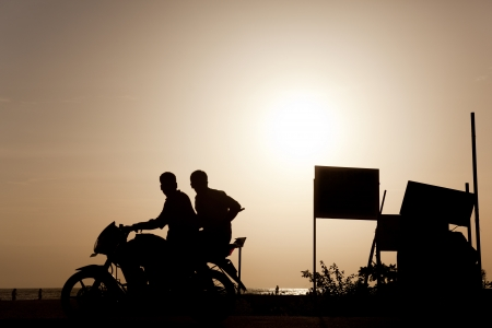 allepey: Backlight of a motorcycle with two people on the beaches of allepy Stock Photo