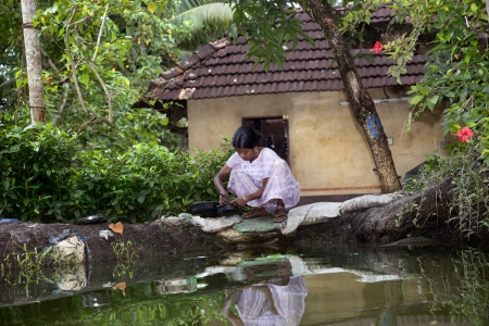Allepy, India-September 7, 2012. Indian woman washes dishes and cutlery on the edge of one of the canals of Alappuzha Stock Photo - 17044928