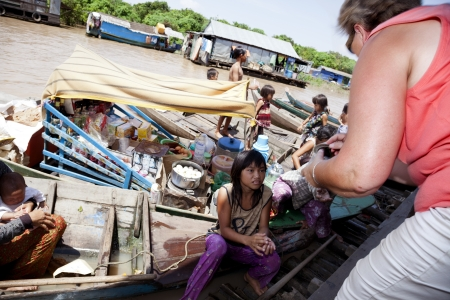 Chong Kneas, Cambodia-   Many tourists visit a floating village near Siem Reap  The villagers are coming up with their boats to tourists and they throw them candy and useless things thinking that help them with their charity