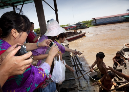 worthless: Chong Kneas, Cambodia- Many tourists visit a floating village near Siem Reap  The villagers are coming up with their boats to tourists and they throw them candy and useless things thinking that help them with their charity