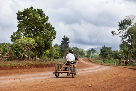 traveled: The roads between small towns in Laos are unpaved and are less traveled. A couple on a motorcycle traveling on a dirt road