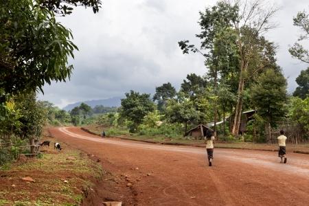 reiste: Paksong, Laos-28. Juli 2009. Die Stra�en zwischen den kleinen St�dten in Laos sind nicht asphaltiert und sind weniger gereist. Zwei M�dchen zu Fu� auf einem Feldweg