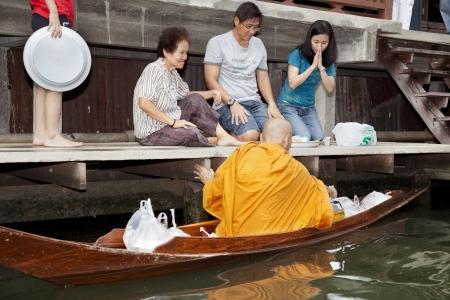 Damnoen Saduak, Thailand-August 9, 2009: Every day very early in the morning, dozens of monks leave with their boats on the canals to beg