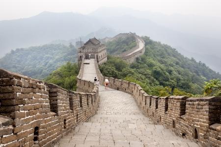 muralla china: Beijing, China, 17 de agosto 2010 Miles de turistas visitan diariamente la muralla china Una familia caminando en la Gran Muralla de China de que el horizonte se pierde en la niebla Foto de archivo