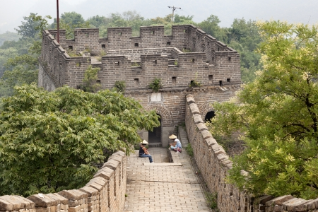 Thousands of tourists visit daily the Chinese wall  Two women resting from the long walk  One look at his cell Stock Photo