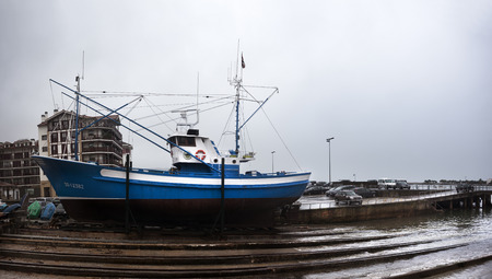 Hondarribia, Spain-December 20, 2014: During winter with bad weather a fishing boat on a dock waiting to be prepared to remove it afloat