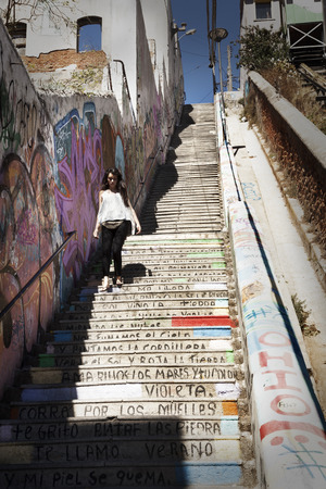 poems: Valparaiso, Chile-February 5, 2014: The streets in Valparaiso are like a artworks by their graffiti and poems written on the walls. A girl descends the stairs of one of the hills where there is a poem written in his steps Editorial