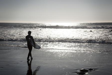 iluminado a contraluz: Concón, Chile 6 de junio de 2015: Surfer paseos por la playa después de un tiempo de diversión en el agua. La imagen es retroiluminado y cuenta con el sujeto en silueta.