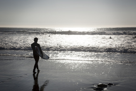 backlit: Concon, Chile-June 6, 2015: Surfer walks along the beach after a fun time in the water. Image is backlit and features the subject in silhouette.