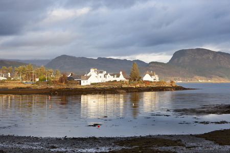 highlands region: Small village on the shores of Loch Carron and a small island off the west coast village of Plockton, in Scotland, is home to a small number of trees and the occasional seal. Stock Photo