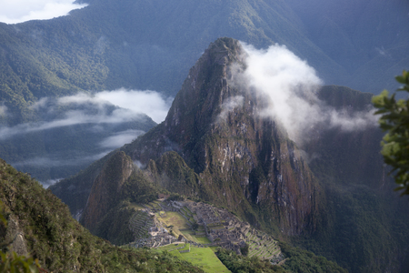 conquistador: Spiritual morning mist rises over Inca head mountain at Machu Picchu with Huana Picchu in background.