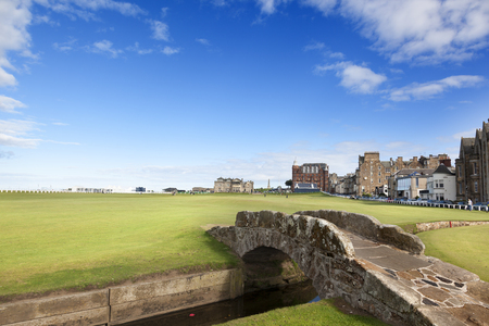 St.Andrews-Scotland, september 14, 2013: The famous Swilken Bridge on the Royal and Ancient Golf course, St Andrews Scotland with Clubhouse and Hamilton Hall in background