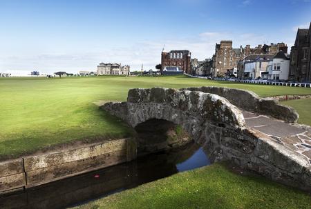 St.Andrews-Scozia, 14 settembre 2013: Il famoso Ponte Swilken sul percorso Royal and Ancient Golf, St. Andrews in Scozia con Clubhouse e Hamilton Hall di sfondo Archivio Fotografico - 52639960