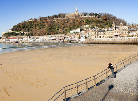 Donosti, Spain-December 22, 2014: On sunny days, the people of Donosti take the opportunity to stroll along La Concha Beach
