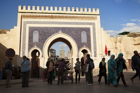 Fez, Morocco-March 24, 2014: The Bab Bou Jeloud is a recent addition to Fes El Bali, having been built around 1913. The Medersa Bou Inania minaret is framed by this impressive gateway into the Medina