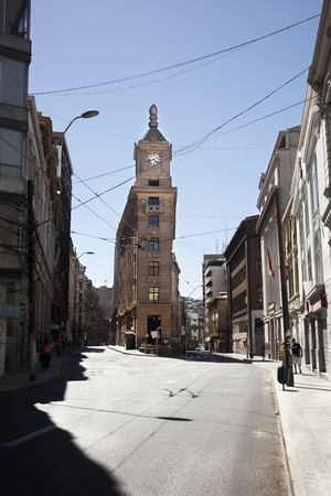 Valparaiso, Chile-February 02, 2014: Watch Turri building in the middle of the street, downtown of valparaiso in a sunny day, and some tourist walking around Editorial