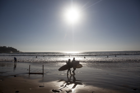 Concon, Chile-June 6, 2015: Surfer walks along the beach after a fun time in the water. Image is backlit and features the subject in silhouette.