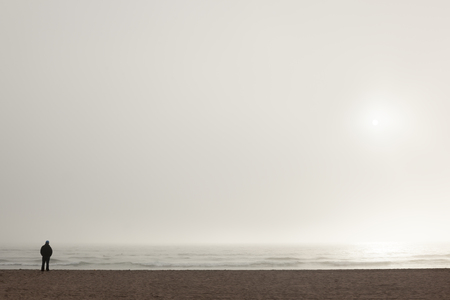 A man looks at the horizon on the beach covered by fog
