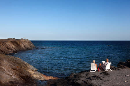 Menorca, Spain-August 27, 2015:  A couple looking at the Mediterranean from a cliff on the Island of Menorca Editoriali