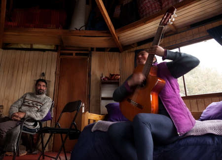 Melipeuco, Chile: May 1, 2015: An artist plays her guitar plays in a wooden house for her friends Editoriali