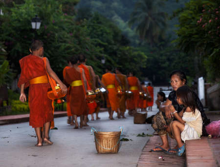 Luang Prabang, Laos-July 23, 2009. Every day very early in the morning, hundreds of monks walk the streets to beg