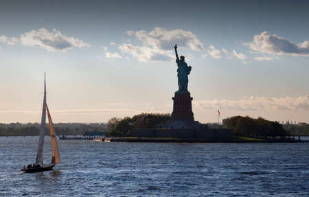 New York, USA-June 08, 2017: Sunset behind The statue of Liberty as a sailing ship approaches to visit it Editoriali