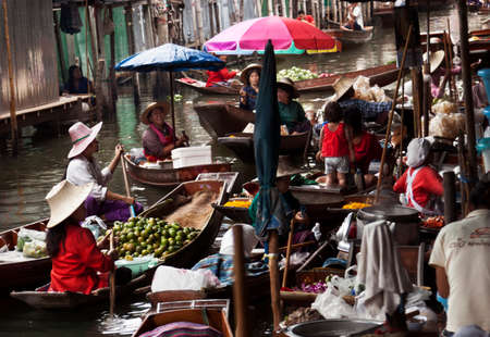 Damnoen Saduak, Thailand-August 9, 2009: People sells souvenirs from his boat at a floating market near Bangkok Editoriali