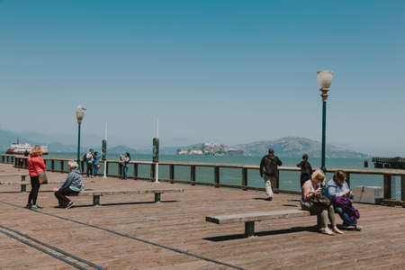San Franciso, CA, USA-June 21, 2017: Tourists resting on the pier in front of the Alcatraz jail Editoriali