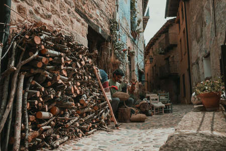 Valderrobres, Spain. April 24, 2021: Craftsman working on a basket of esparto grass at his point of sale in the old town of Valderrobres