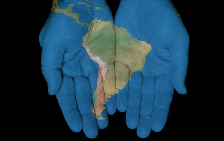 Map painted on hands showing concept of having South America in our hands  photo